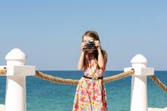 Een meisje fotografeert met een camera in een rode kleding tegen het overzees stock foto