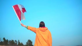 Een meisje in een geel jasje en glazen houdt in haar hand de vlag van Canada De vlag van Canada ontwikkelt zich in de wind stock footage