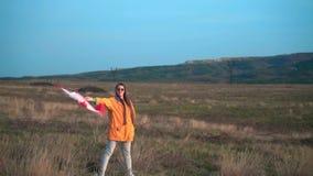 Een meisje in een geel jasje en glazen houdt in haar hand de vlag van Canada De vlag van Canada ontwikkelt zich in de wind stock video