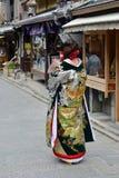 Een meisje is gekleed in een mooie KIMONO Stock Afbeelding