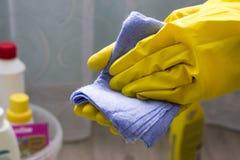 Een meisje in gele handschoenen houdt een vod, close-uphuishoudelijk werk royalty-vrije stock fotografie