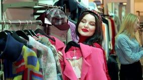 Een meisje in gescheurde jeans en een rode sweater kiest kleren in een moderne opslag stock video