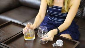 Een meisje giet alcohol van een karaf in een glas stock footage
