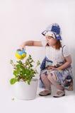 Een meisje giet bloemen Stock Afbeeldingen