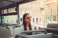 Een meisje in glazen met lang donker haar zit binnen een sightseeingsbus, onderzoekt de camera en glimlacht stock foto's