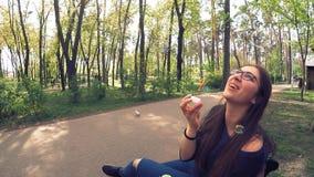 Een meisje in glazen speelt zeepbels in het park stock video