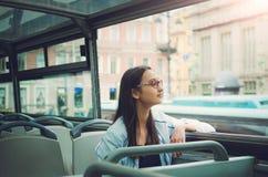 Een meisje in glazen zit binnen een reisbus en onderzoekt de camera en kijkt uit het venster stock afbeeldingen