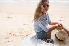 Een meisje in glazen zit op het strand Royalty-vrije Stock Foto