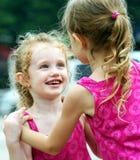 Een meisje glimlacht Adoringly bij Haar Zuster royalty-vrije stock afbeelding