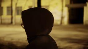 Een meisje in een grijze laag met een kap op haar hoofd is op nachtstad De atmosfeer van een nachtgang De mening van over haar sc stock footage