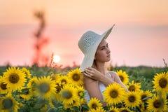 Een meisje in een grote hoed op een zonnebloemgebied bij zonsondergang Royalty-vrije Stock Foto's