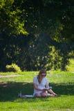 Een meisje in het park zit op het gras en leest een boek Stock Fotografie