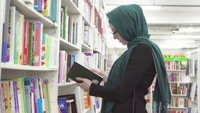 Een meisje in een hijab in een bibliotheek of een boekhandel stock footage