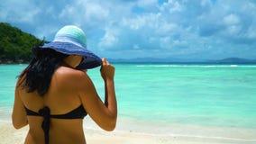 Een meisje in een hoed die naar het turkooise water op het witte zandstrand gaan stock videobeelden