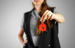 Een meisje houdt de sleutels aan het huis Sleutelring rood huis stock fotografie