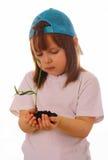 Een meisje houdt een installatie in haar handen Stock Foto