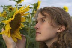 Een meisje houdt en ziet een zonnebloem bij zonsondergang Stock Fotografie