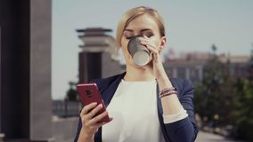 Een meisje houdt een glas met koffie, onderzoekend een rode smartphone Het meisje heeft een witte blouse en een jasje, is zij stock video