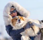 Een meisje houdt een hond in haar wapens in de winter royalty-vrije stock foto's