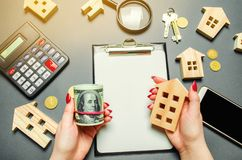 Een meisje houdt in zijn handen dollars en een miniatuurhuis Het concept risicoberekening voor de aankoop van onroerende goederen royalty-vrije stock foto