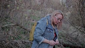 Een meisje in jeans gaat onder een boomtak die haar hoofd buigen over Mooi cinematic kader Langzame playback stock video
