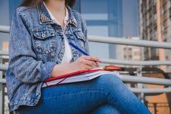 Een meisje in jeanskleren zit op een bank, houdt notitieboekjes en schrijft Voor de straat, schrijft zij in een notitieboekje, be stock afbeelding