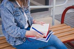 Een meisje in jeanskleren zit op een bank, houdt notitieboekjes en schrijft Voor de straat, schrijft zij in een notitieboekje, be stock foto