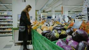 Een meisje kiest de groenten in de supermarkt in Italië stock footage
