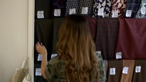 Een meisje kiest een stof in een weefselopslag stock videobeelden