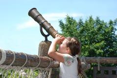 Een meisje kijkt door een telescoop Royalty-vrije Stock Afbeeldingen