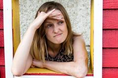 Een meisje kijkt uit het venster van een blokhuis en kijkt uit voor iets met een ontstemde uitdrukking Zij heeft gewacht en l Stock Foto's