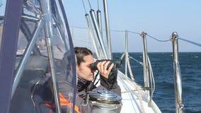 Een meisje kijkt in verrekijkers op een jacht stock videobeelden