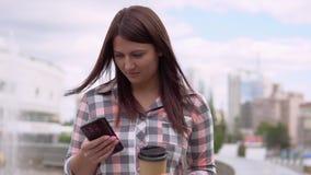 Een meisje in een kleding zit dichtbij een fontein in het park en gebruikt een smartphone Langzame Motie Close-up stock videobeelden