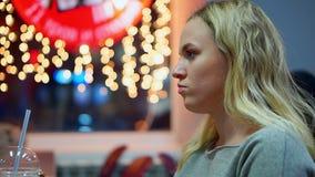 Een meisje in een koffie veegt haar handen met een nat servet af De achtergrond van de Bokeh gloeilamp stock video