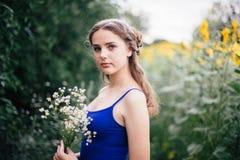 Een meisje in korte borrels en een blauwe T-shirt met een boeket van wilde bloemen royalty-vrije stock afbeelding