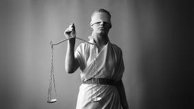 Een meisje in een kostuum van het steenstandbeeld Femida de godin van rechtvaardigheid op een witte achtergrond die in één hand d stock video