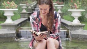 Een meisje leest een boek en lacht stock videobeelden