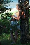 Een meisje leunt tegen een boom, kustlijn stock fotografie