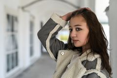 Een meisje in een lichte schapehuidlaag bij de colonnade royalty-vrije stock afbeeldingen