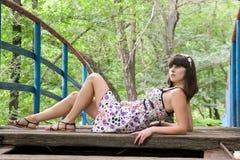 Een meisje ligt op een brug Stock Foto's