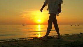 Een meisje loopt blootvoets langs een zandig overzees strand in een witte kleding op een zonsondergangachtergrond Het meisje loop stock video