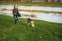 Een meisje loopt met een hond langs de dijk Mooie schor hond De rivier De lente Royalty-vrije Stock Afbeeldingen