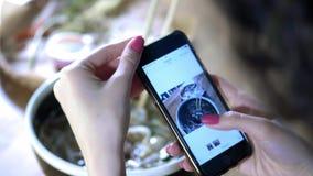 Een meisje maakt een foto van voedsel op smartphone Aandeel met vrienden een foto van voedsel in sociale netwerken Koffie met Azi stock videobeelden