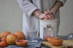 Een meisje maakt verse grapefruit juice royalty-vrije stock afbeelding