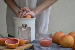 Een meisje maakt verse grapefruit juice royalty-vrije stock afbeeldingen
