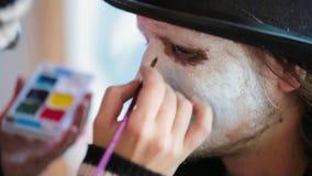 Een meisje in make-up trekt make-up op een mens stock video