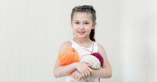 Een meisje met ballen van draad voor het breien royalty-vrije stock afbeeldingen