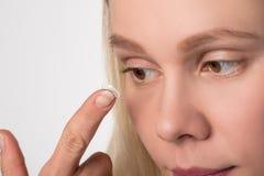 Een meisje met bruine ogen draagt een contactlens voor visie stock fotografie