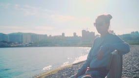 Een meisje met donker haar in een grijze sweater en glazen zit op een bank door het overzees Hemelachtergrond, overzees, cityscap stock footage