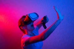 Een meisje met een gamepad die in vrglazen, met blauw en rood licht spelen Het concept innovatie en de toekomst stock afbeelding